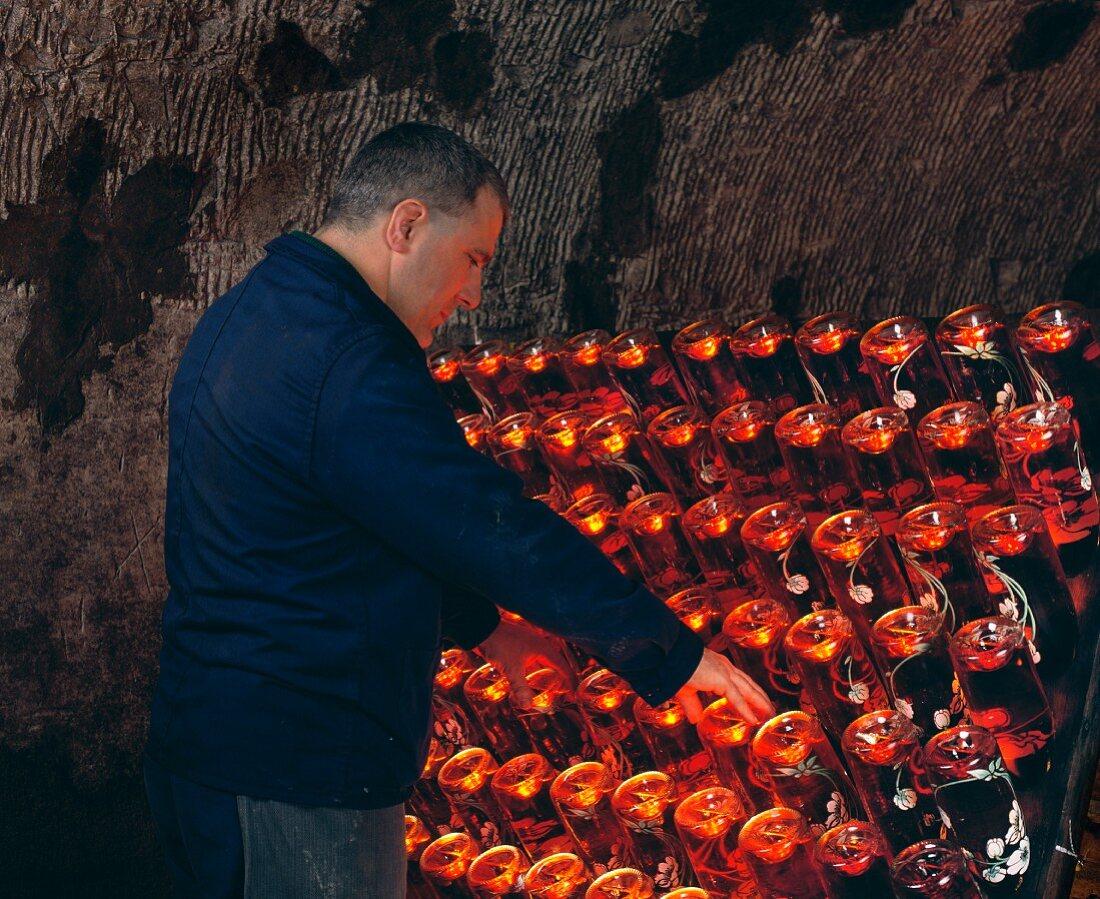 Arbeiter einer Champagner-Kellerei an einem Rüttelpult stehend