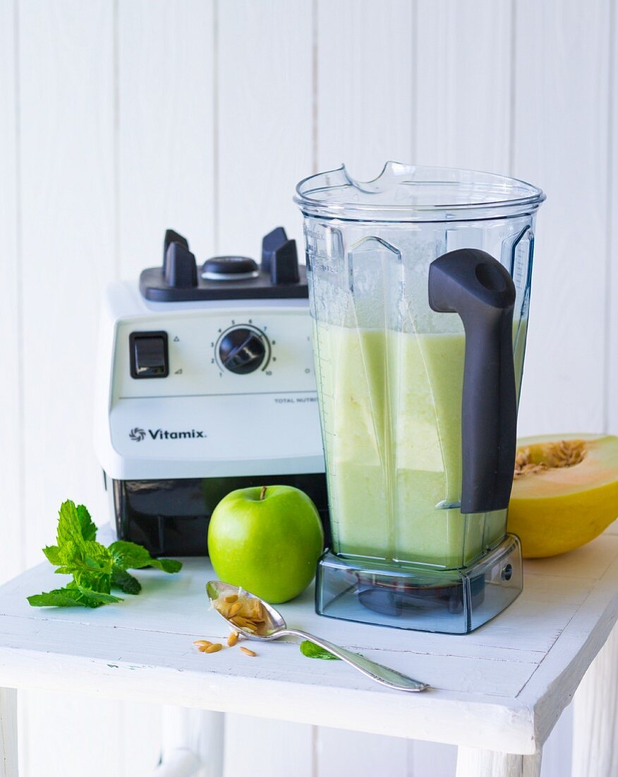 A smoothie made with cucumber, melon and apple being made in a mixer