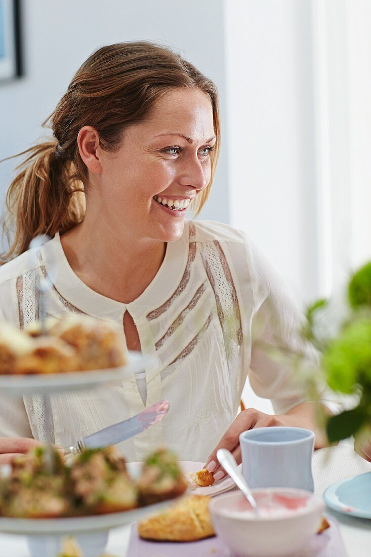 A laughing woman sitting at a dining table