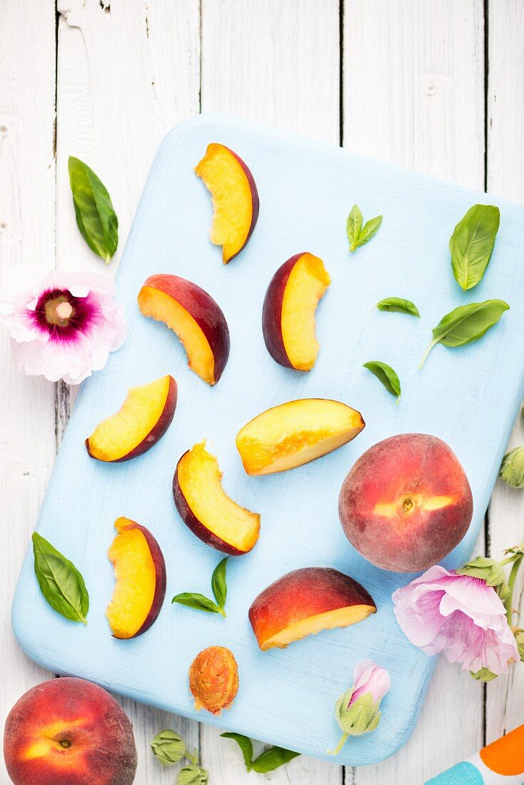 Peaches, whole and sliced, on a chopping board