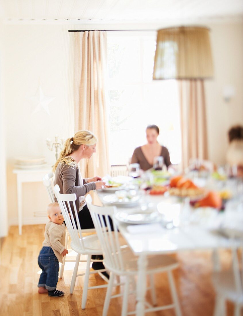 Two women and a small child at a table laid for Thanksgiving
