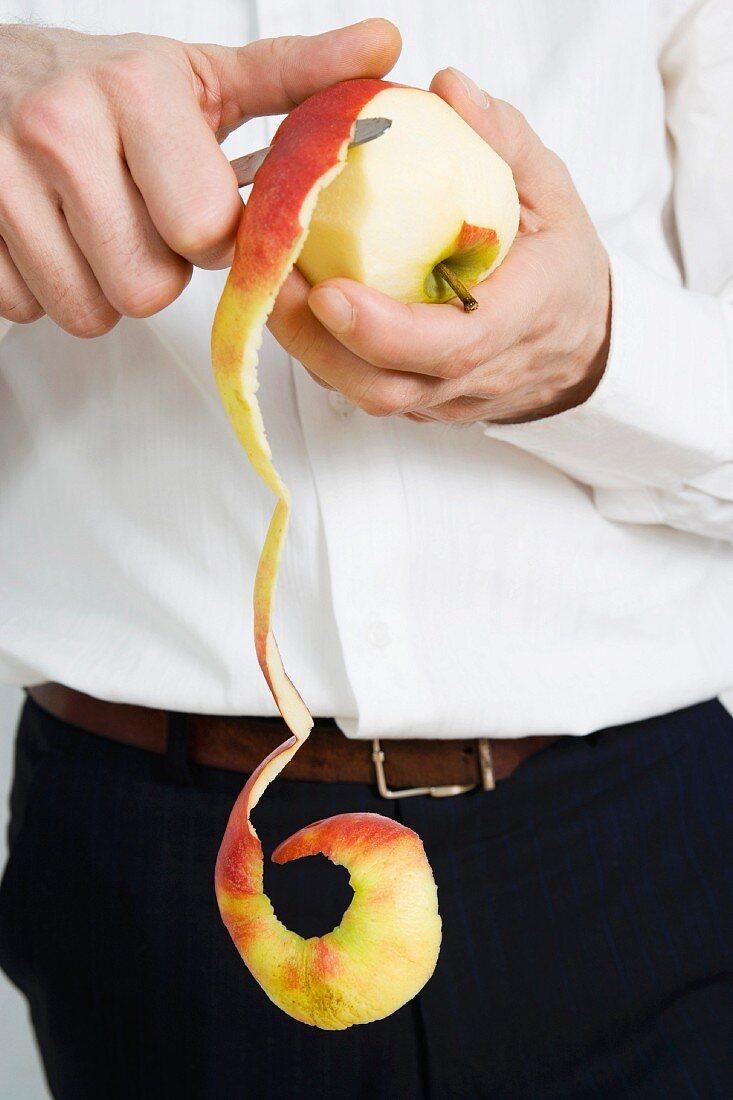 A man peeling an apple