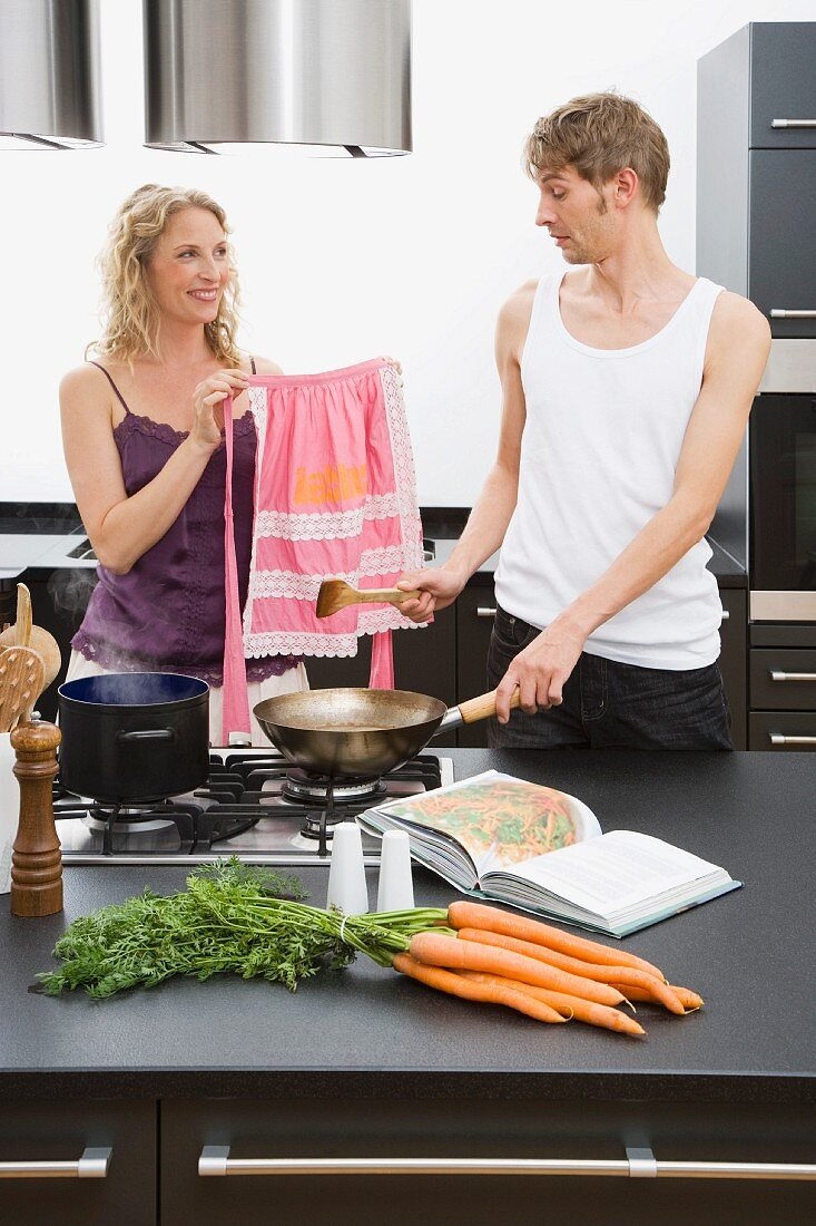 A woman showing a man a pink apron