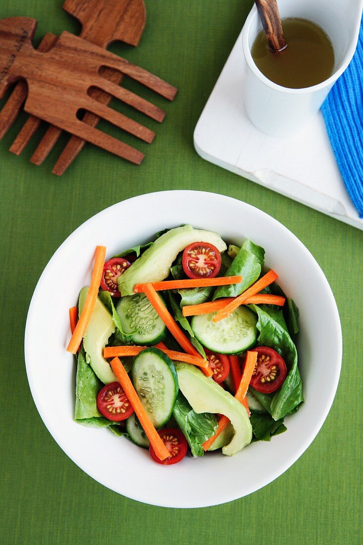 A garden salad with cucumber, avocado, carrots and cherry tomatoes