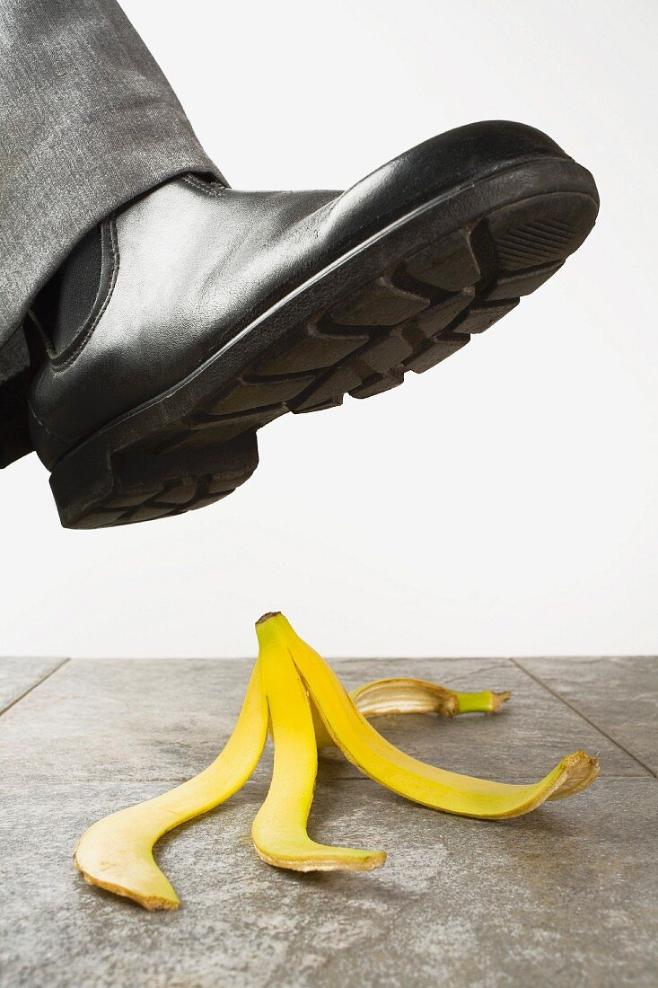 A foot wearing a boot about to tread on a banana peel
