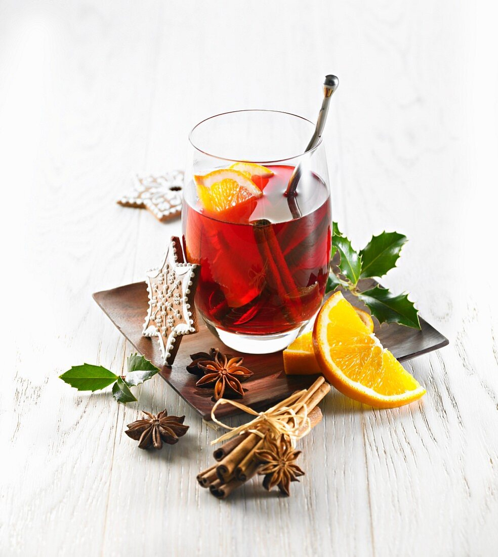 A glass of mulled wine with cinnamon and orange slices
