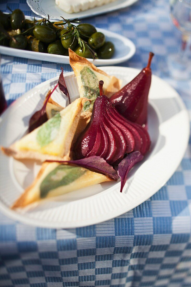 Cheese toast triangles with preserved pears and olives on a garden table
