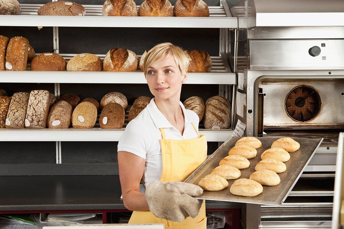 A woman holding a tray of freshly baked rolls in a bakery