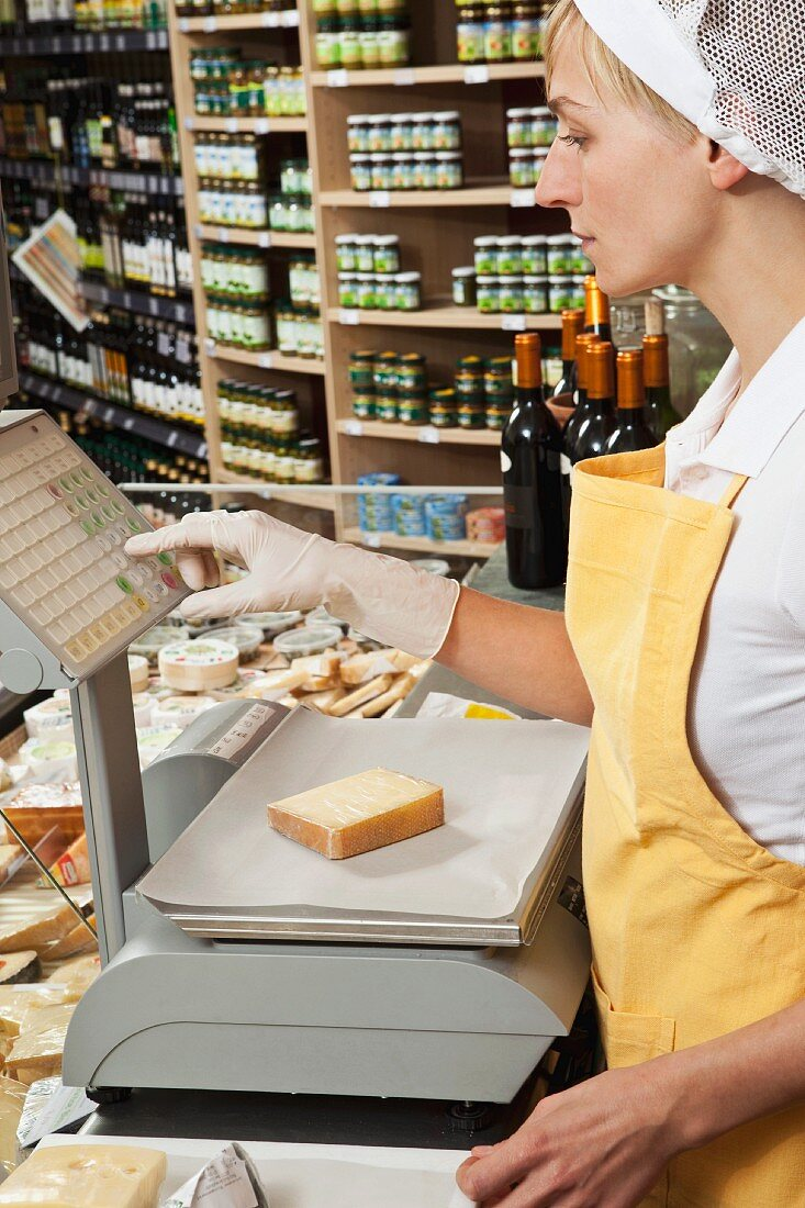 Verkäuferin wiegt ein Stück Käse im Lebensmittelladen