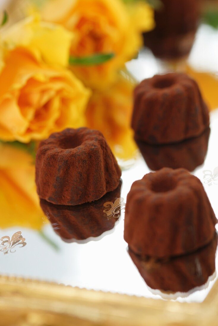 Chocolate pralines on a mirrored tray with orange coloured roses in the background
