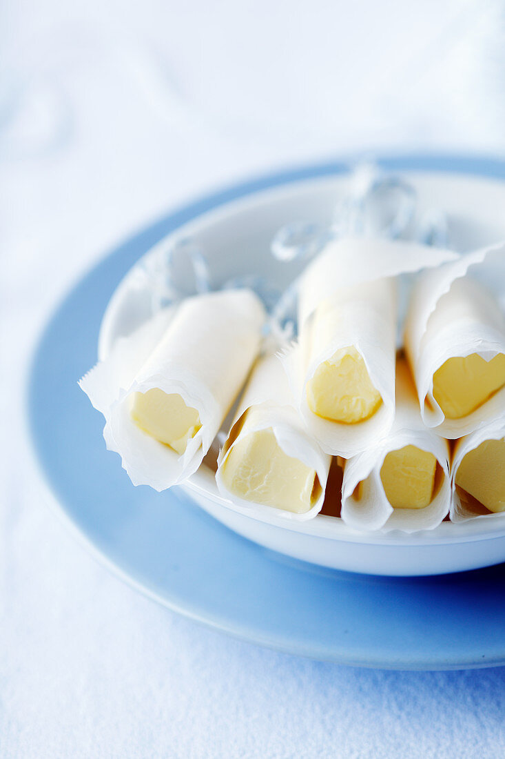 Rolls of butter wrapped in paper
