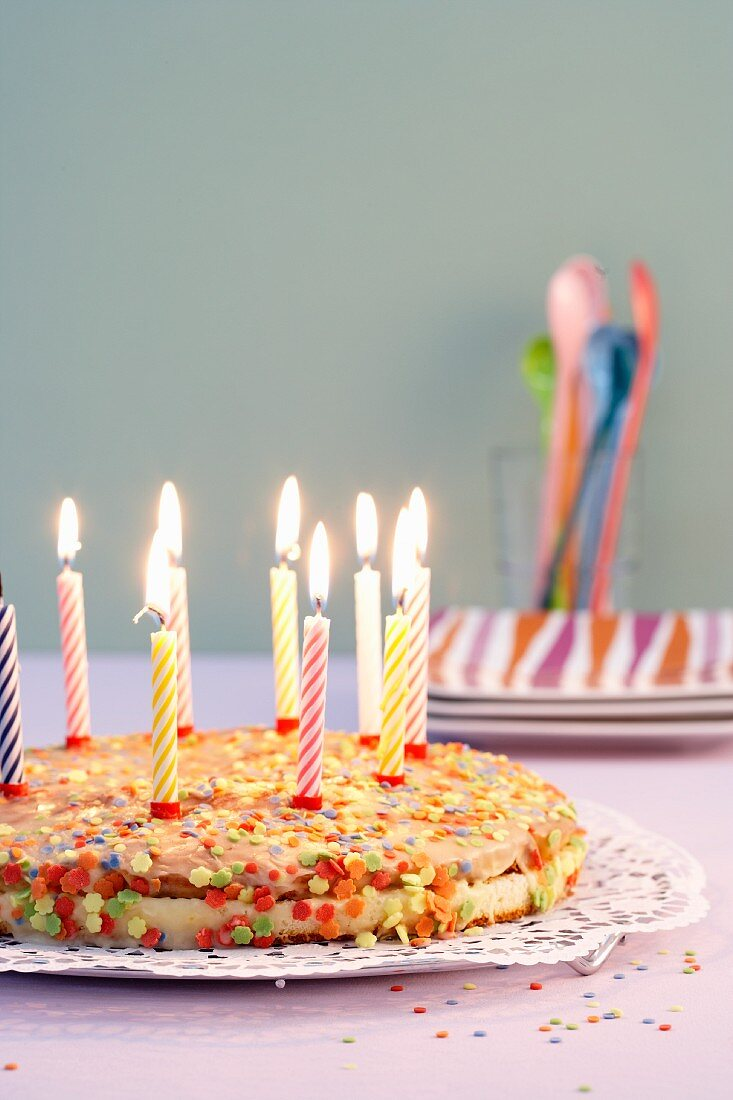 A birthday cake with candles and sugar sprinkles