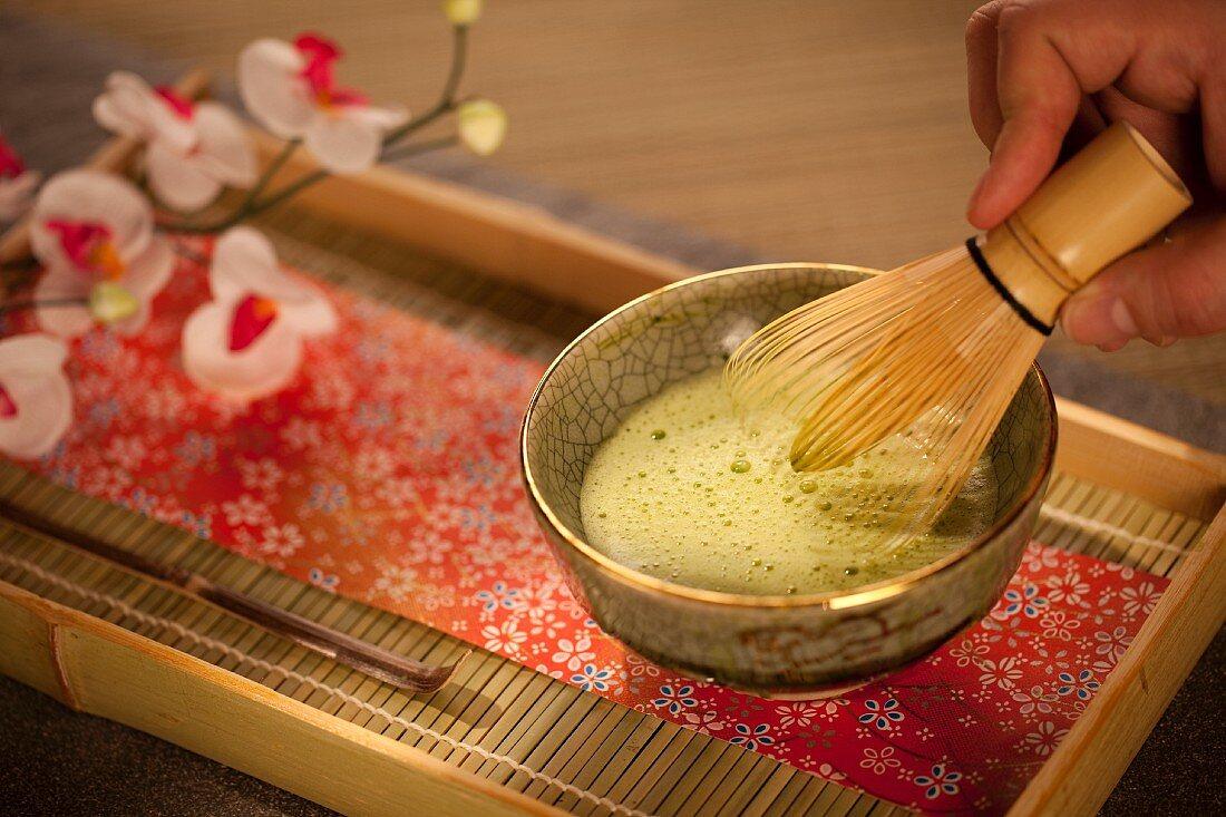 Matcha-Tee mit einem Matchabesen anrühren