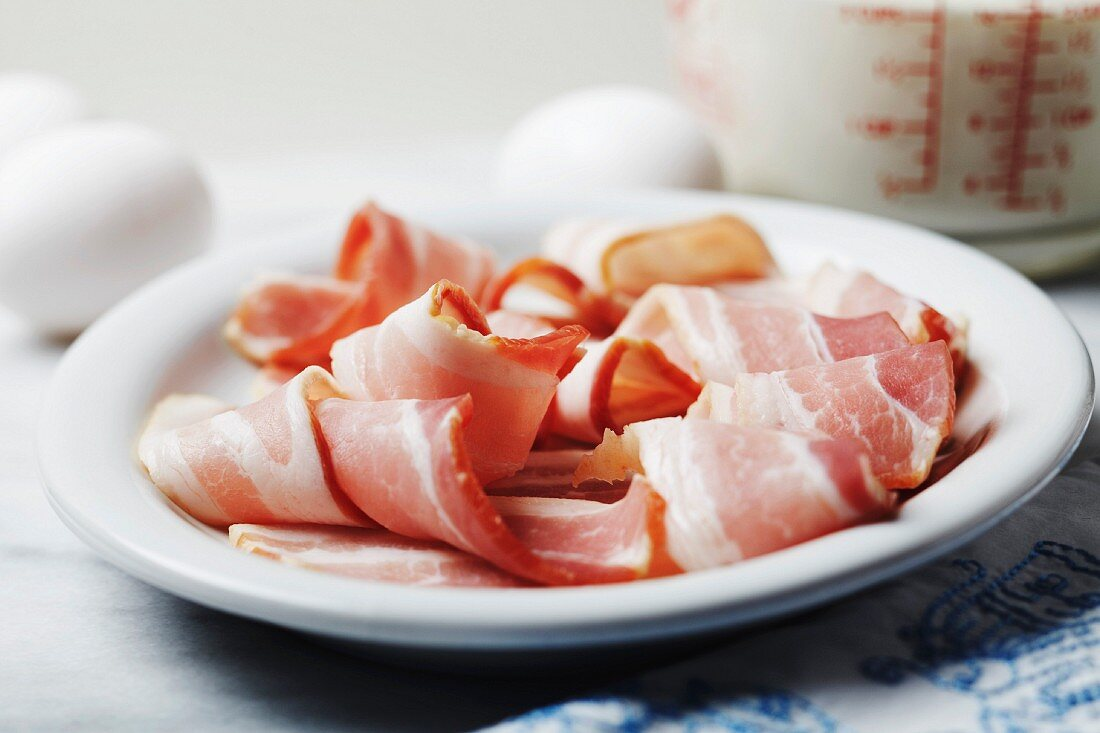 Breakfast Ingredients; Strips of Uncooked Bacon, Eggs and Milk