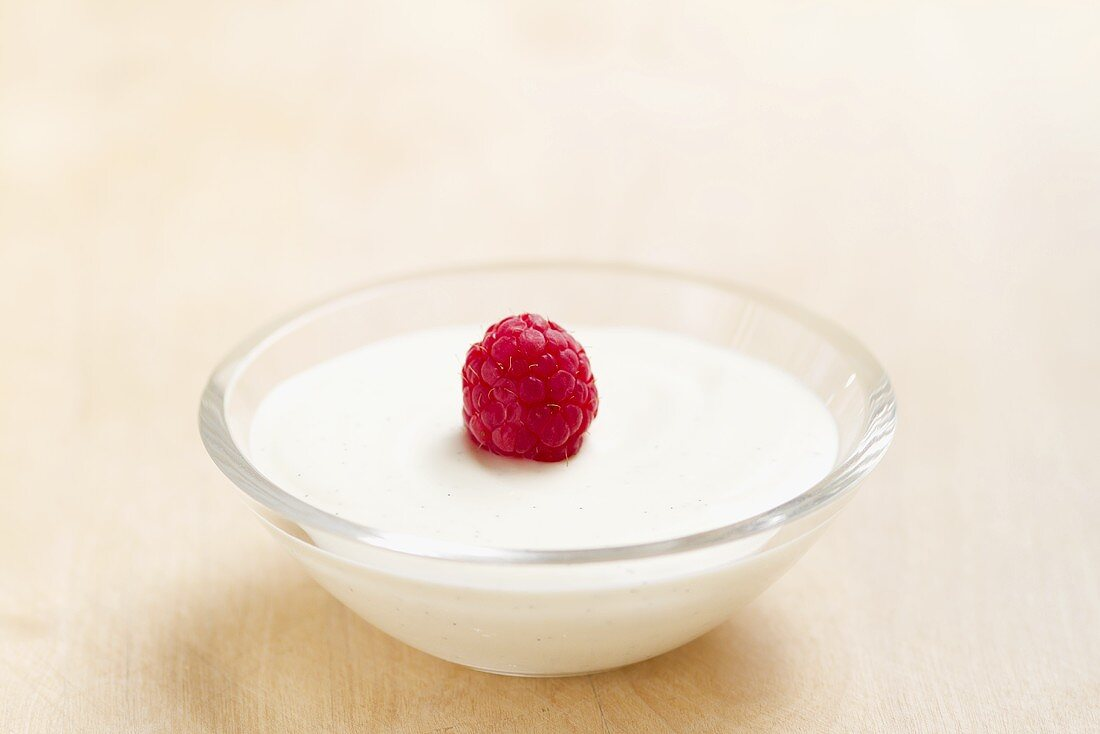 Vanilla cream in a bowl topped with a raspberry