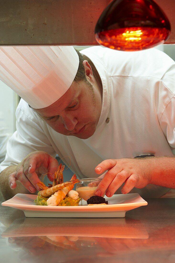 A head chef serving prawns on avocado tartar with a dip