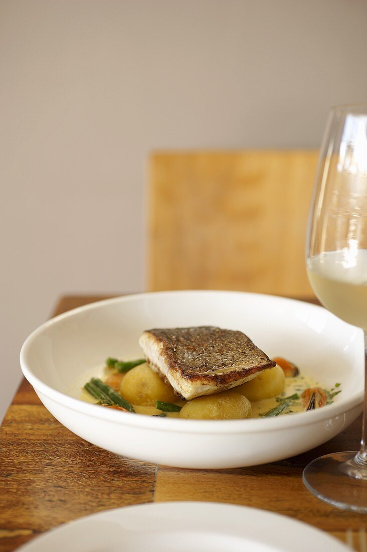 Hake with new potatoes, green beans and a mussel and saffron sauce