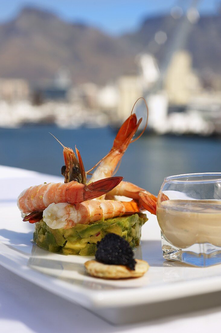 Prawns on avocado tartar and a blini with caviar and a dip