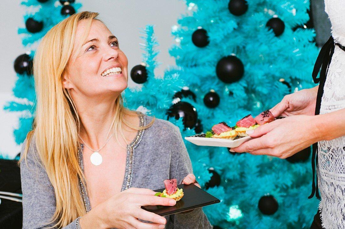 A woman eating a Christmas canapé