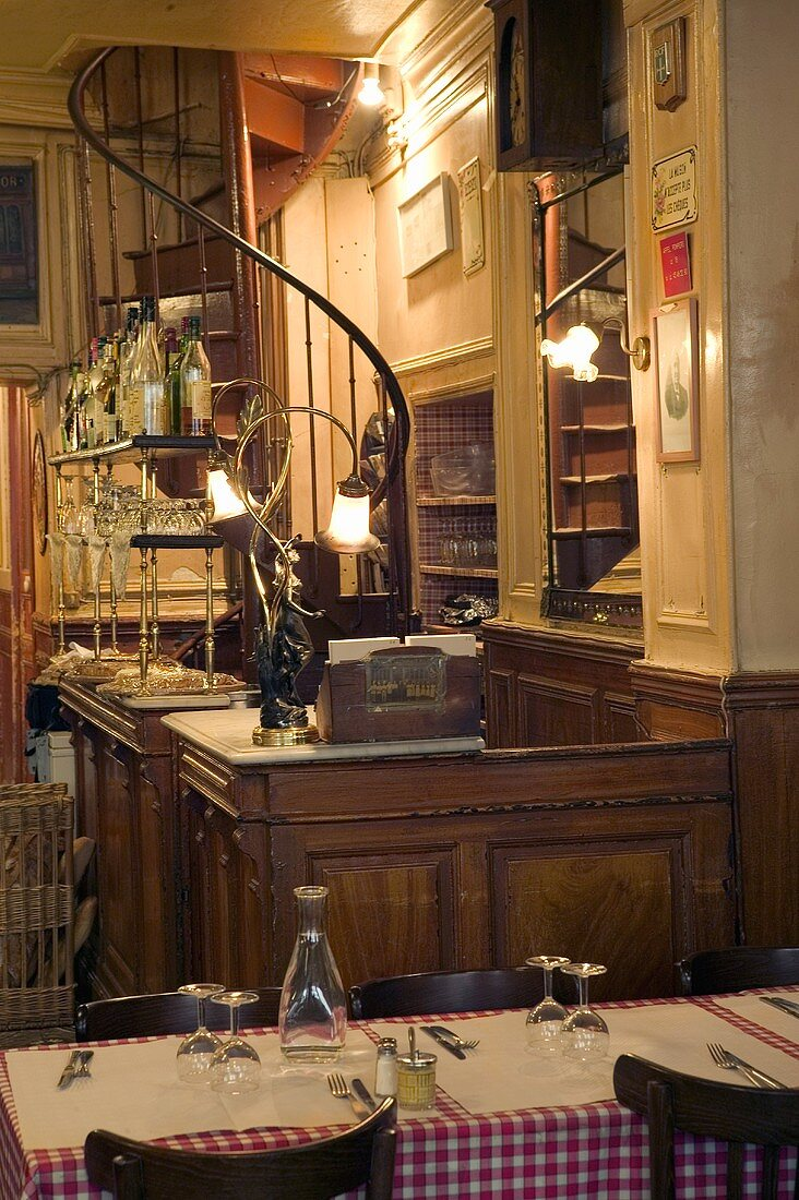 A table laid at the reception of a restaurant with a spiral staircase in the background
