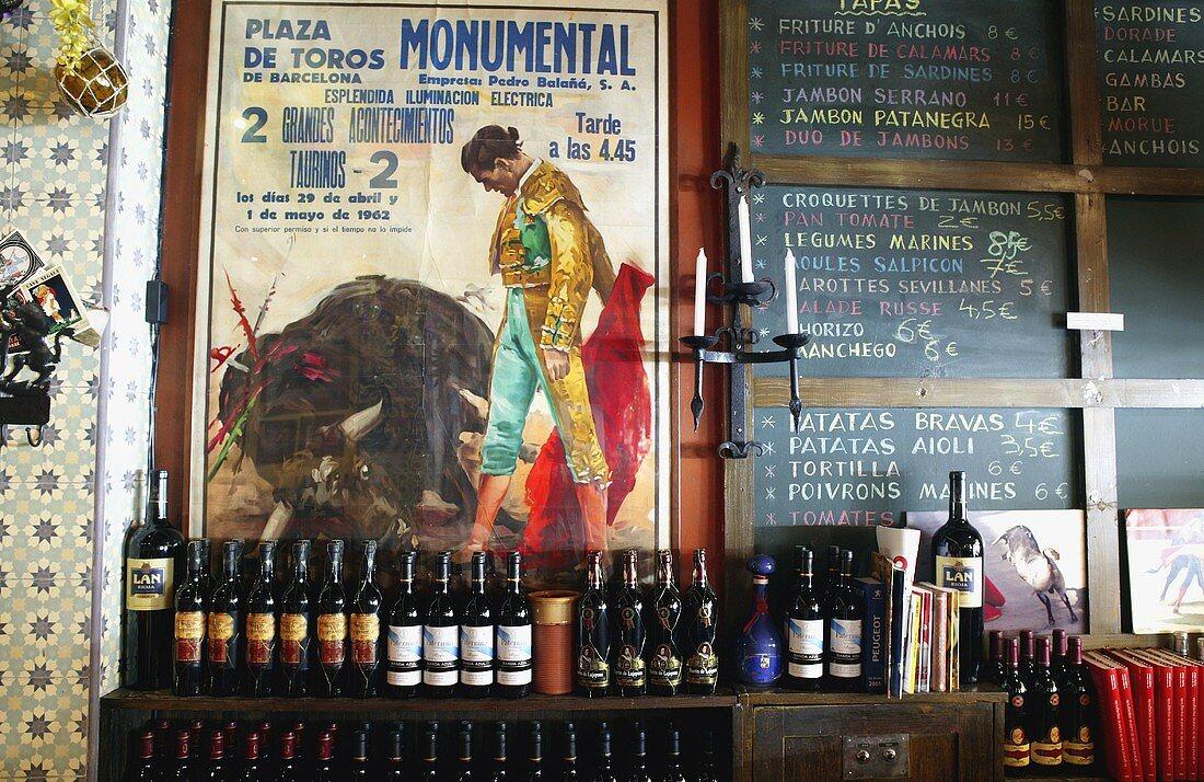 Wine bottles on a shelf in front of a poster and a menu written on a blackboard