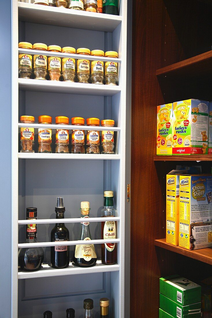 A white spice rack in a niche next to an open shelf stacked with food
