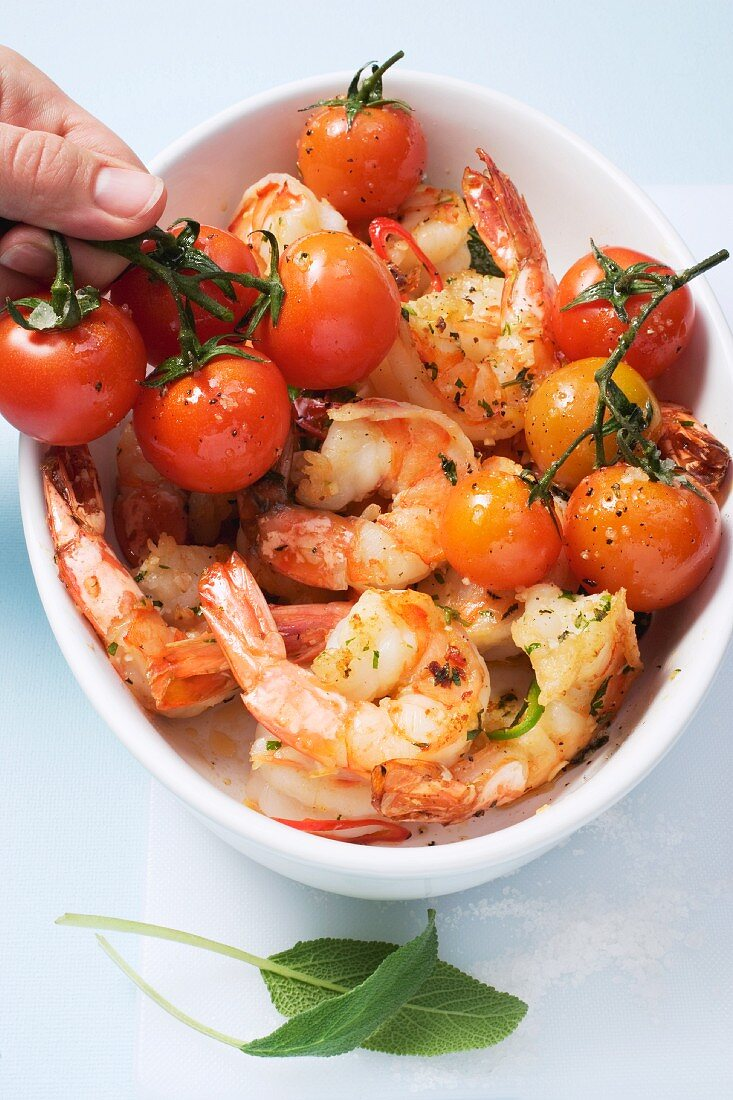 Herb prawns with cherry tomatoes being placed in an oven proof dish