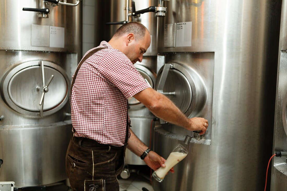 A brewer taking a beer sample from a storage tank