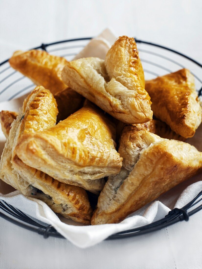 Cheese-filled puff pastry parcels in a wire basket