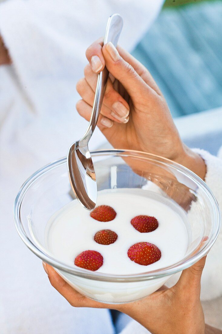 A woman eating yogurt with strawberries