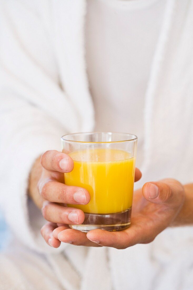 A person holding a glass of orange juice