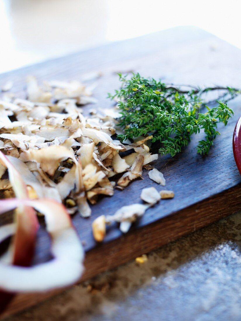 Vegetable peelings, apple peel and thyme on a chopping board