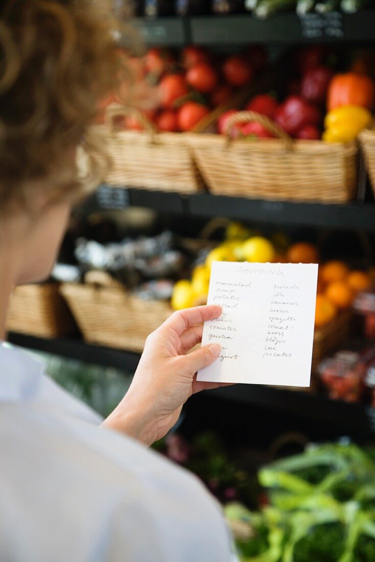 A woman with a shopping list in a supermarket