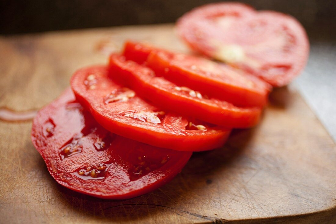 Tomato Sliced on a Wooden Cutting Board