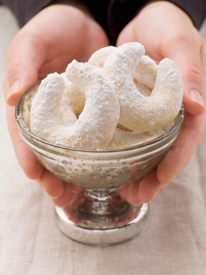 Hands holding silver dish with Vanillekipferl (German vanilla and nut shortbread crescents)
