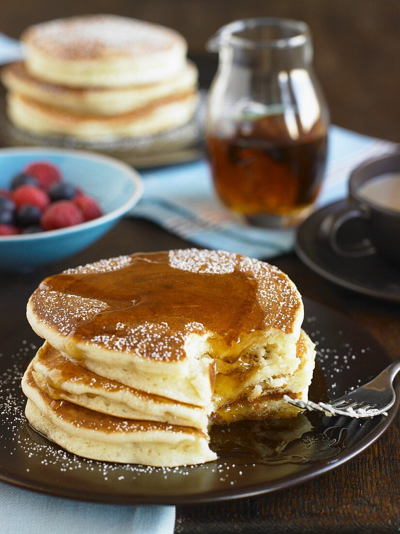 Stack of Buttermilk Pancakes with Syrup and Powdered Sugar; Bite Taken Out