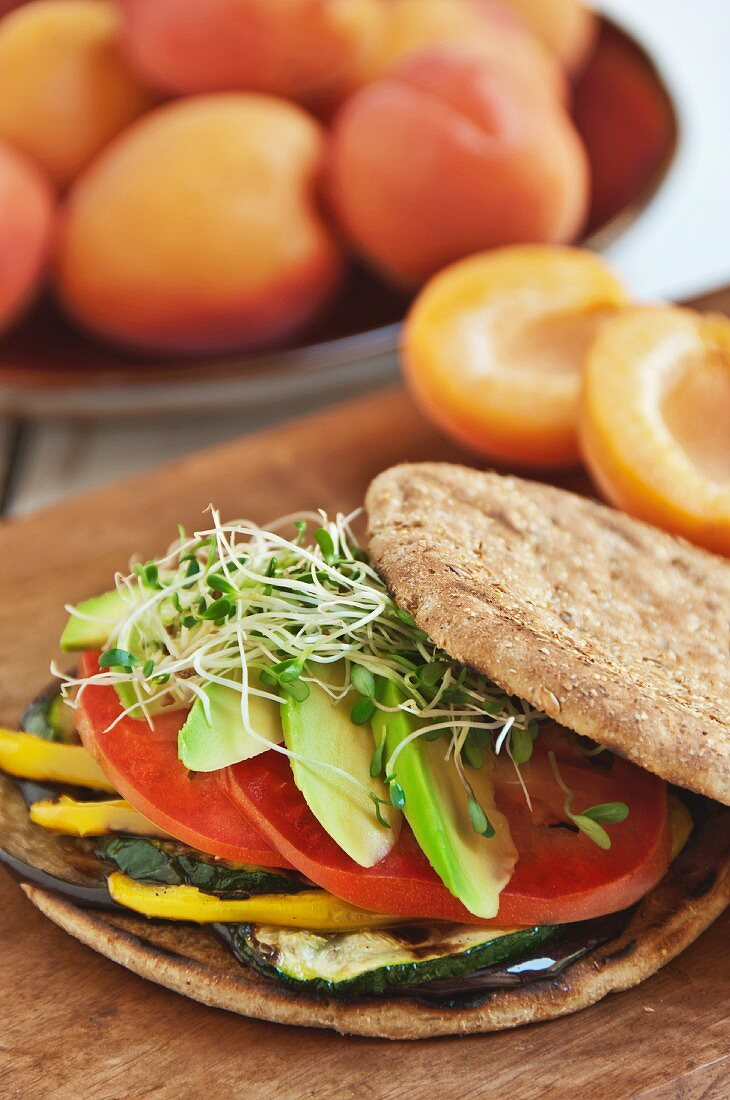 Veggie Sandwich with Grilled Eggplant, Zucchini, Yellow Peppers, Tomato and Avocado on a Flat Round Roll