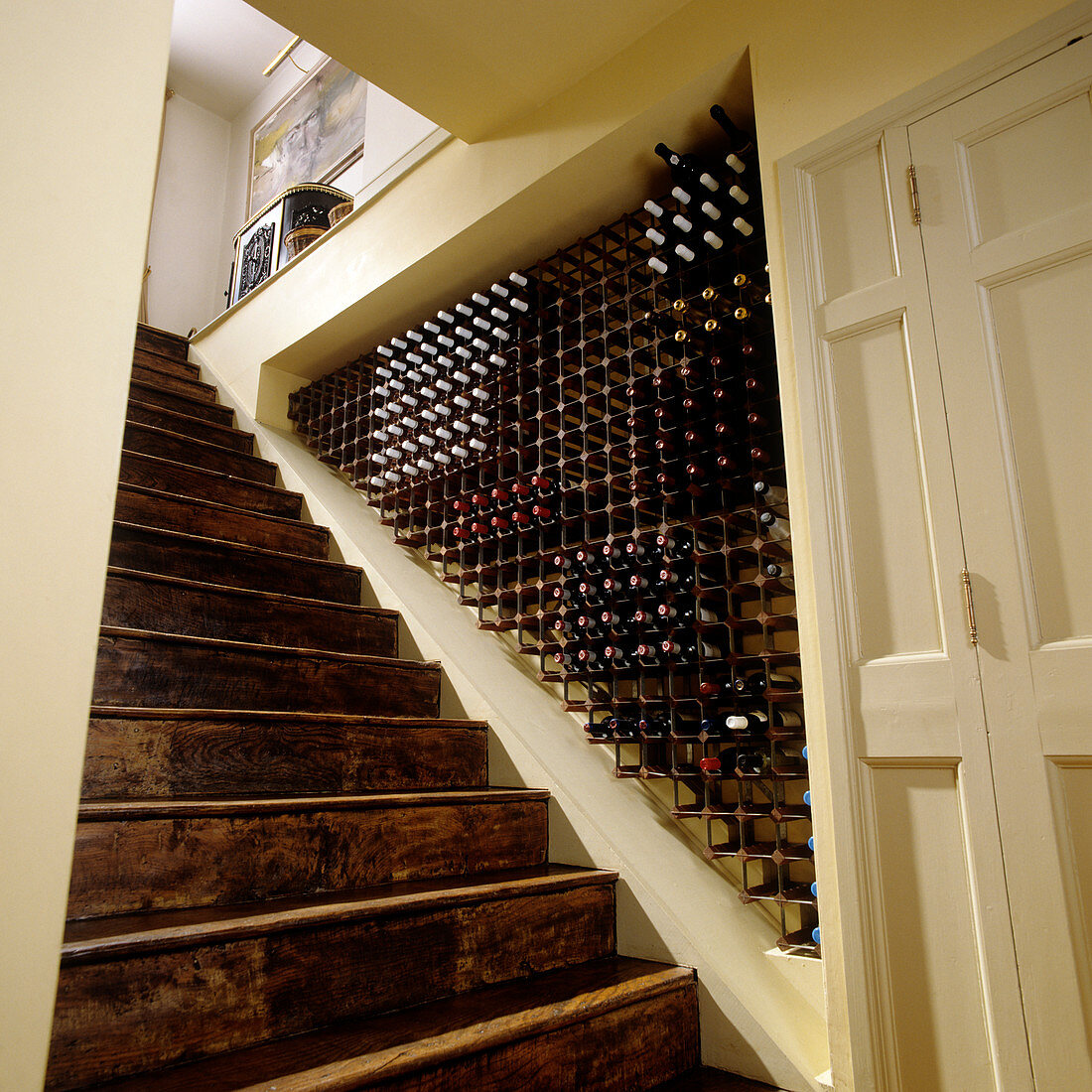 Niche with integrated wine rack alongside old wooden staircase