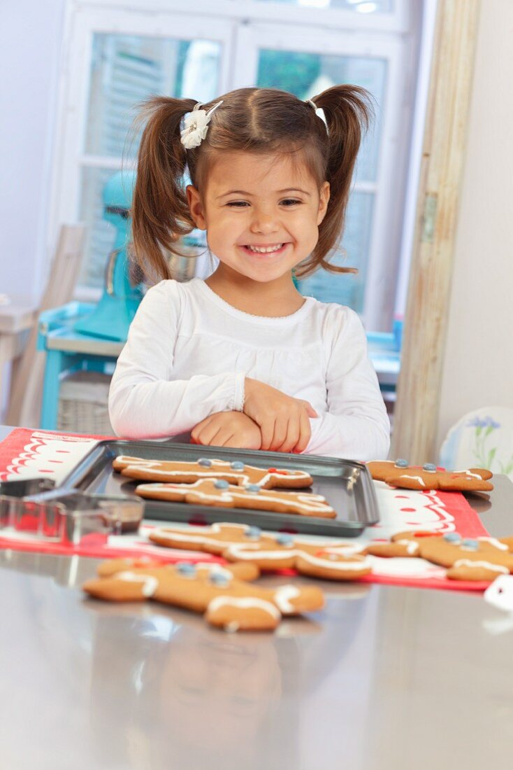A little girl in front of a tray of gingerbread men