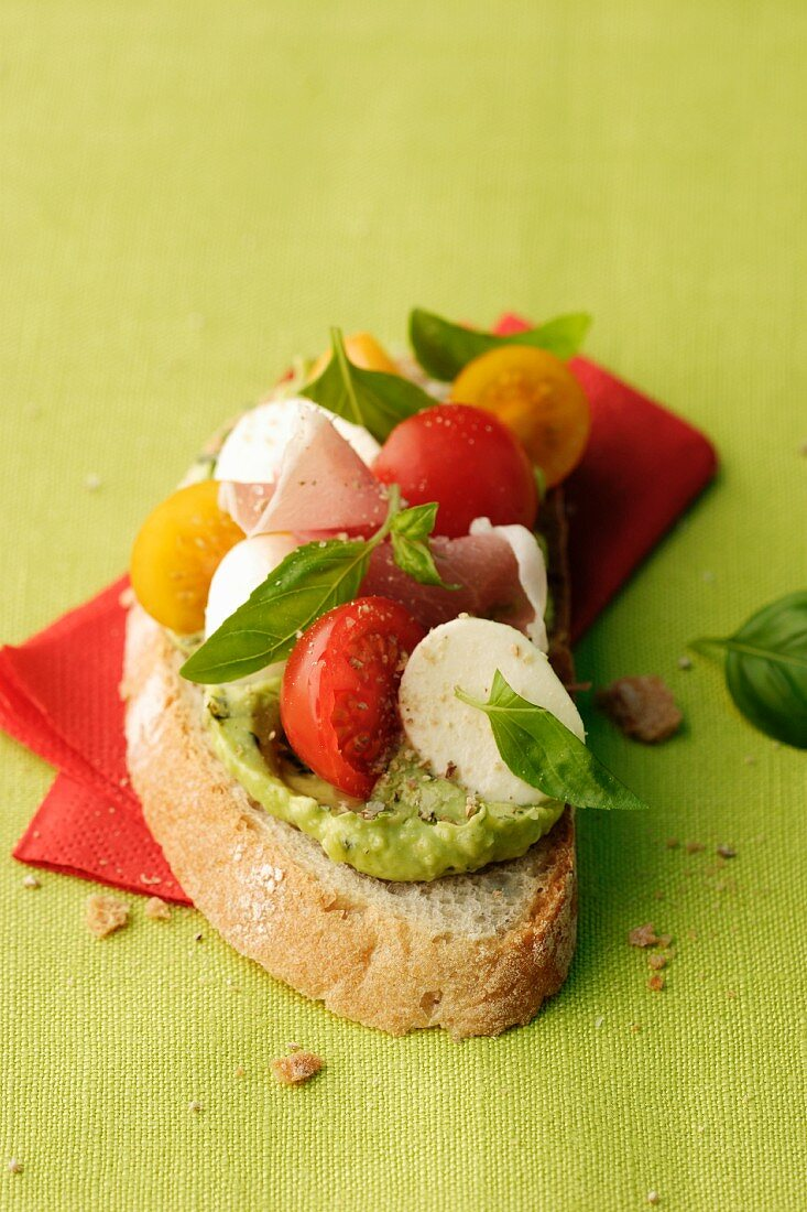 Slice of bread with basil spread, tomatoes and mozzarella
