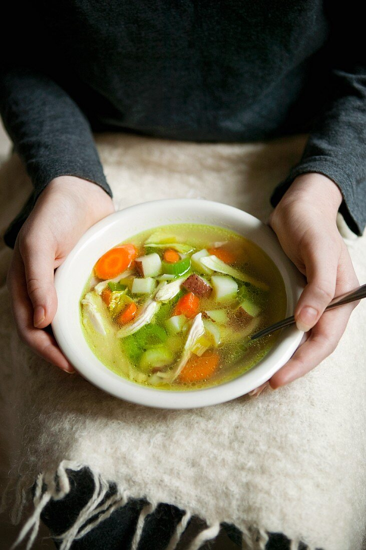 Woman Holding a Bowl of Chicken Soup on Her Lap