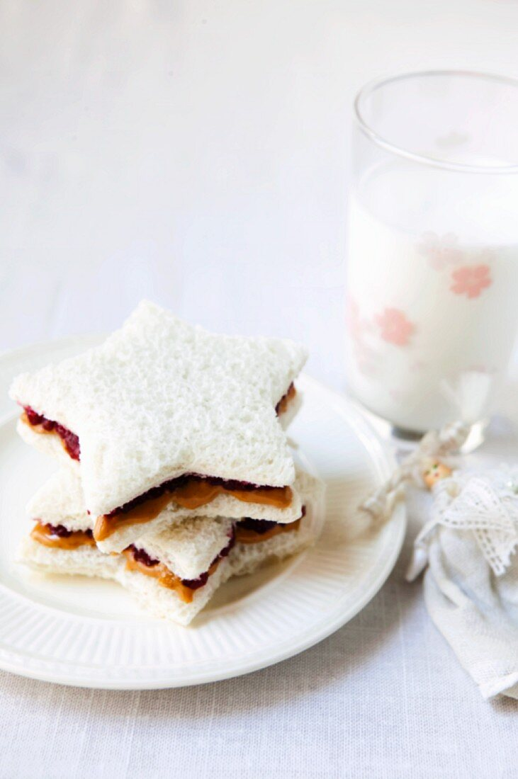 Peanut Butter and Jelly Sandwiches on White Bread Cut Out into Start Shapes; Glass of Milk