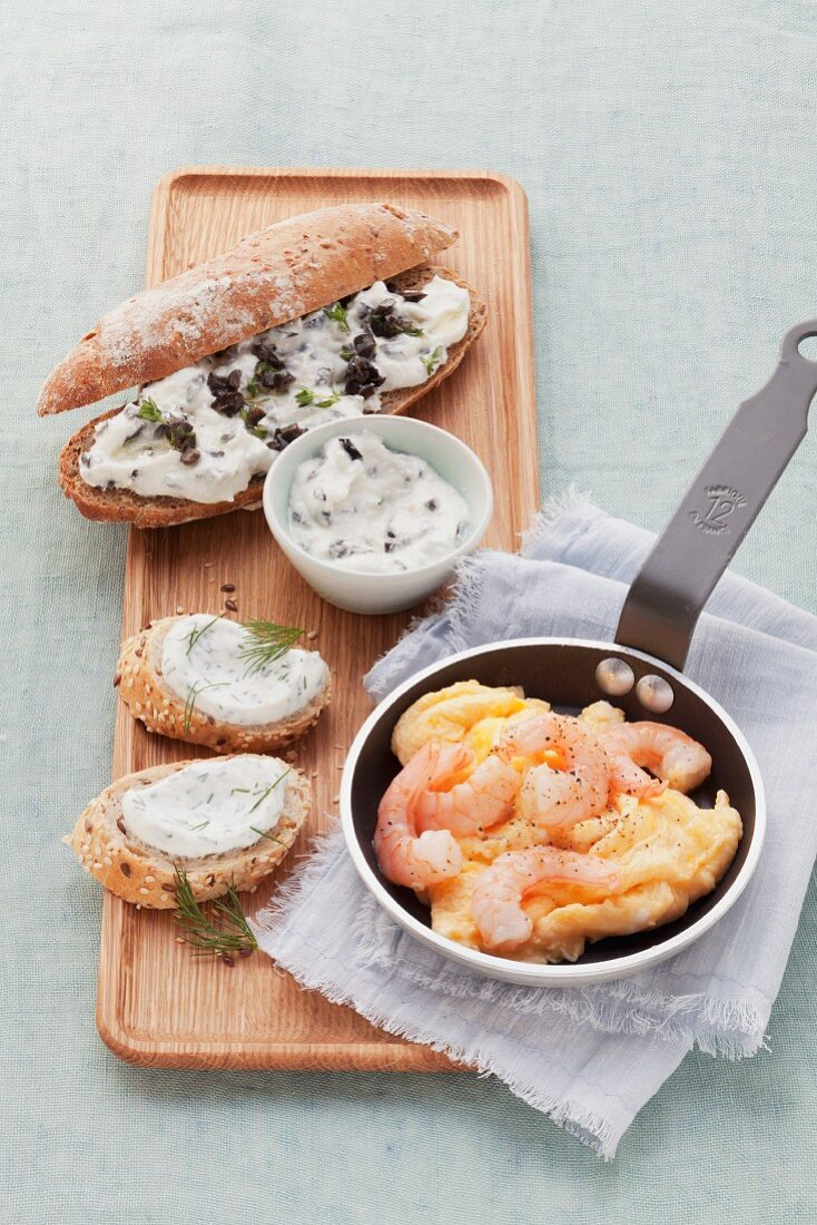Whole wheat rolls with cream cheese, scrambled eggs with shrimp and a whole wheat baguette with dill quark