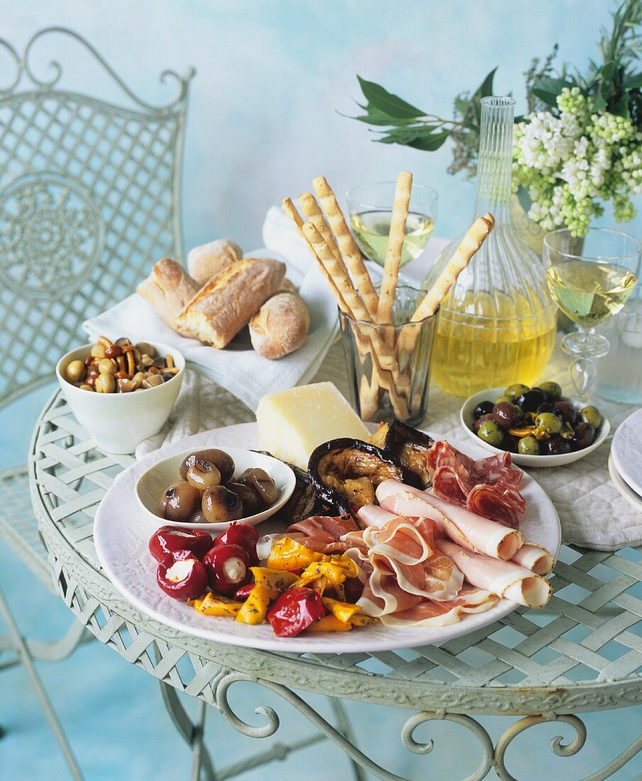 An antipasti platter with ham, preserved vegetables and cheese