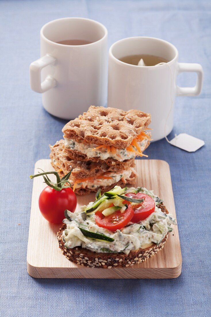 Wholewheat bread with zucchini spread and wholewheat crisp bread with herb quark and grated carrot
