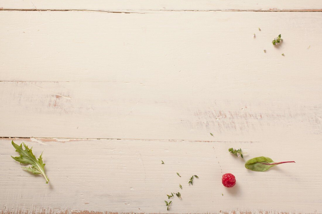 Herb leaves and a raspberry on a wooden background