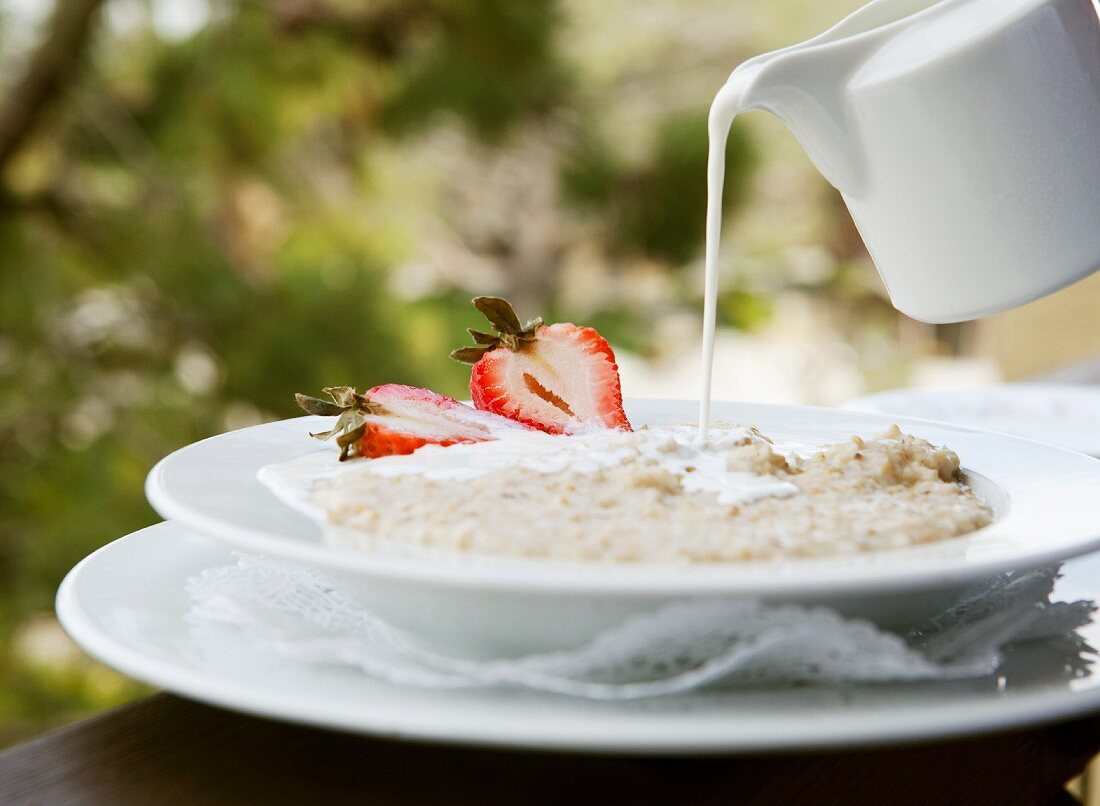 Milk Pouring from a Pitcher onto a Bowl of Oatmeal with Strawberries; Outdoors
