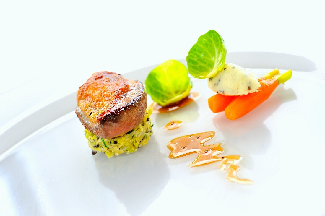 Fried pigeon breast on sprouts with glazed baby carrots