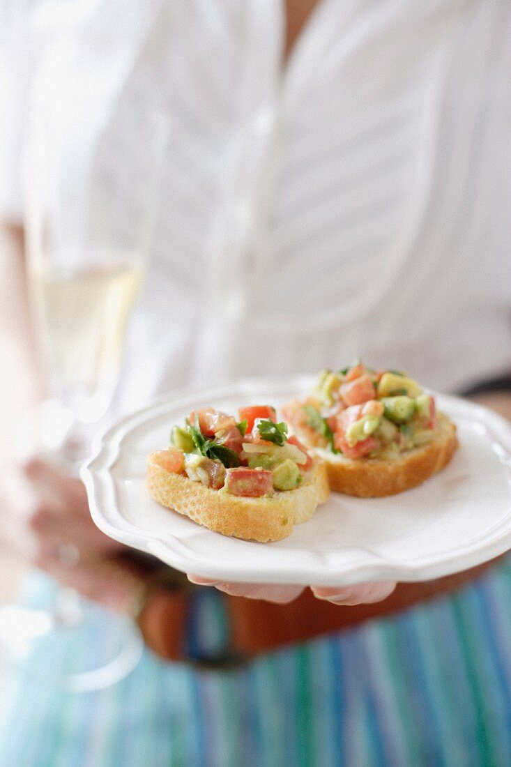 Woman serving baguette slices with avocado and chilli salsa