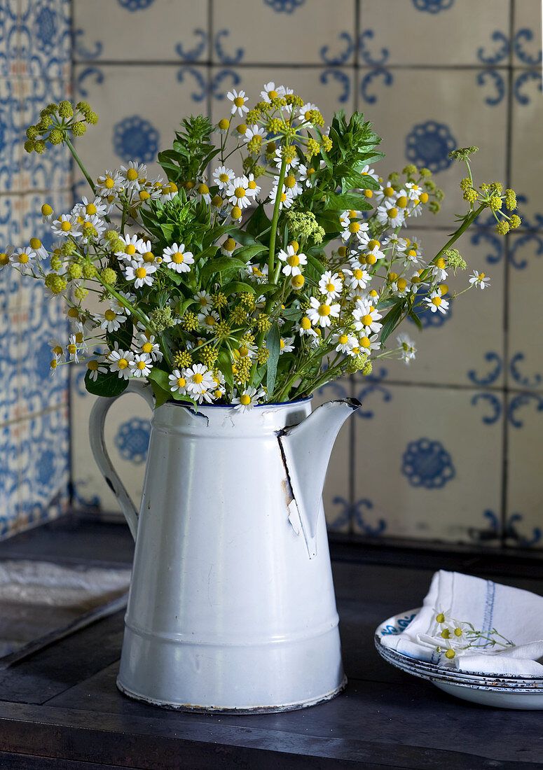 Chamomile flowers in old enamel jug against kitchen tiles in vintage blue and white pattern